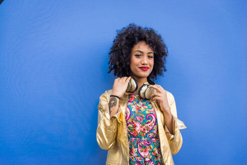 Fashionable Young Woman With Curly Hair Against Blue Background - EYF07811