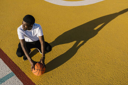 Thoughtful young man holding basketball crouching on sports court during sunny day - EGAF00294