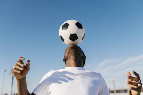 Close-up of young man balancing soccer ball on head against blue sky - EGAF00297