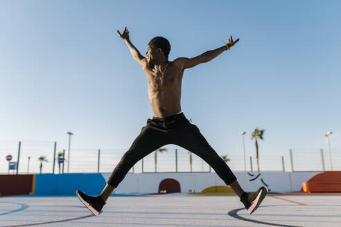 Shirtless young man with arms raised jumping against clear sky in sports court - EGAF00303