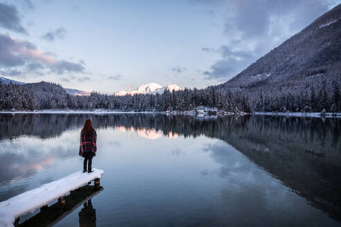 Rear View Of Woman Standing By Lake Against Sky During Sunset - EYF08279