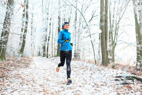 Full Length Of Woman Jogging In Forest During Winter - EYF08321