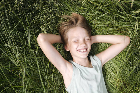 Portrait of happy boy with eyes closed lying on a meadow in summer - EYAF01179