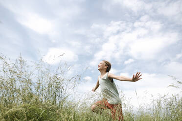 Portrait of happy boy running on a field with arms outstretched - EYAF01182