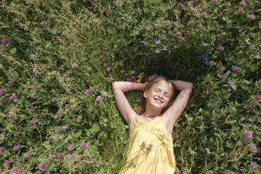 Portrait of happy little girl with eyes closed lying on a meadow in summer - EYAF01188