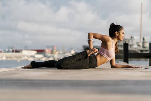 Female athlete practicing half frog pose on pier at harbor - EGAF00338