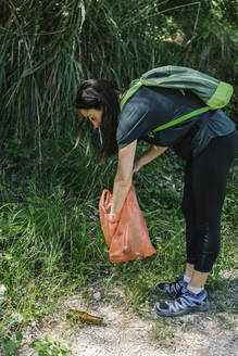 Hiker picking up trash in the woods - XLGF00282