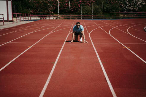 Male athlete in starting position on tartan track - EBBF00229