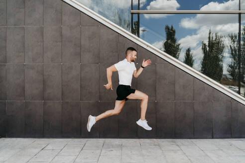 Man running along a building - EBBF00250