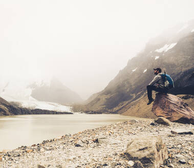 Mature man with backpack looking at lake while sitting on rock, Patagonia, Argentina - UUF20696