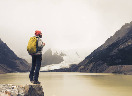 Mature man with backpack standing on rock by lake at Patagonia, Argentina - UUF20702