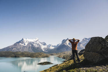 Mature man with backpack sitting on rock by lake at Patagonia, Argentina - UUF20741