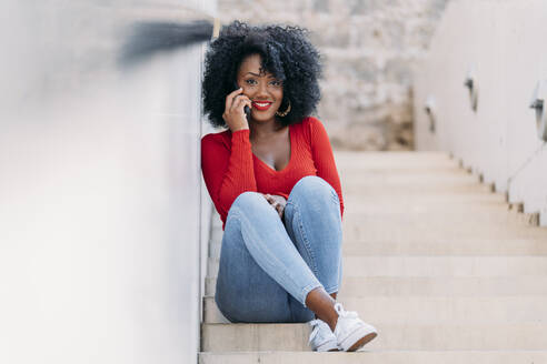 Smiling woman with afro hair using smartphone sitting on stairs - JAF00005