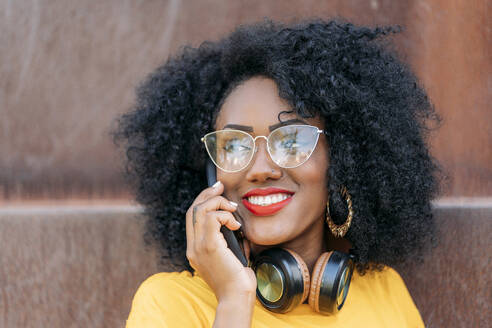 Portait of smiling woman with afro hair using smartphone - JAF00008