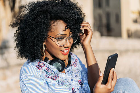 Smiling woman with afro hair and glasses during video call outdoors - JAF00011