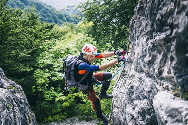 Mountaineer climbing on via ferrata, Orobie, European Alps, Como, Italy - MCVF00482