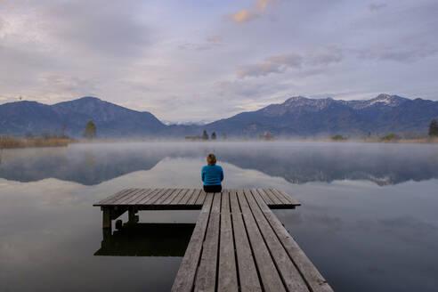 Frau sitzt auf einem Steg, Sonnenaufgang, Eichsee, mit Nebel, Loisachmoor, Kochelseemoor, Großweil, Schlehdorf, Oberbayern, Bayern, Deutschland, - LBF03091