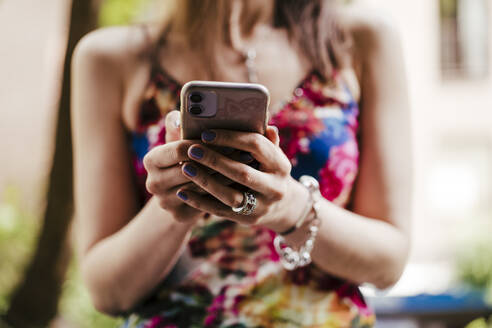 Close-up of woman holding mobile phone - EBBF00295