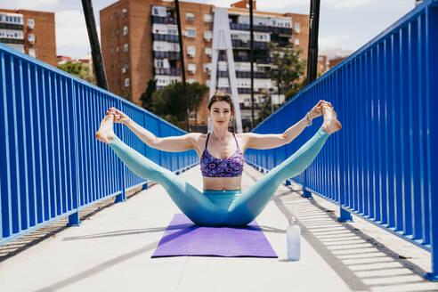 Beautiful woman stretching body while practicing yoga on bridge - EBBF00316