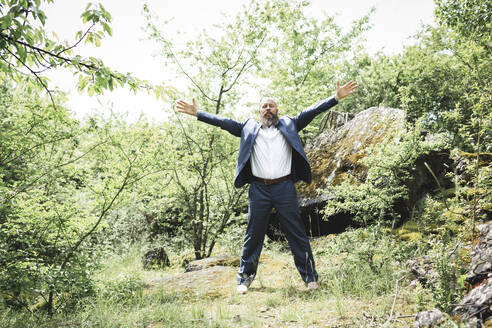 Bearded businessman with arms outstretched exercising on land in forest - HMEF01001