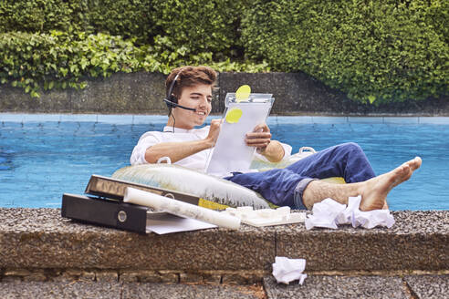 Young man sitting on airbed in swimmingpool and working - UKOF00001