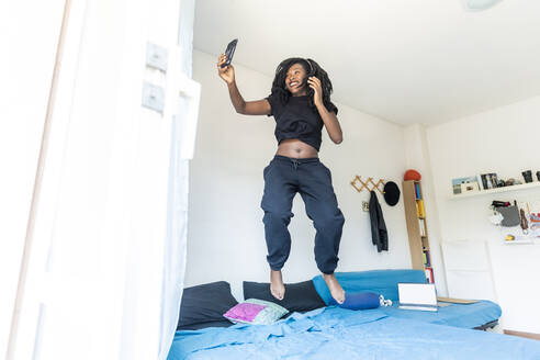 Young woman using smartphone and listening music jumping on bed - MEUF01075