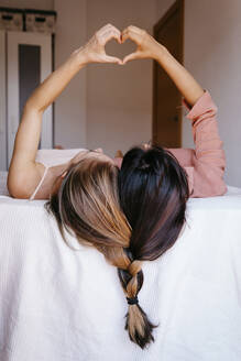 Friends making heart shape with hands while lying on bed - TCEF00802