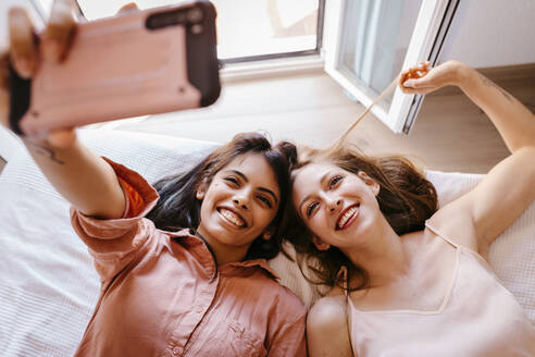 Friends taking selfie with mobile phone while lying on bed at home - TCEF00805