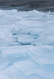 Large flat pieces of ice piled up along the shore of a lake in winter. - CAVF86383