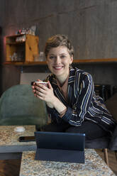 Portrait of smiling freelancer sitting in a coffee shop with digital tablet and smartphone - TAMF02434