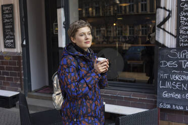 Portrait of daydreaming woman with backpack and coffee to go in front of a coffee shop - TAMF02437