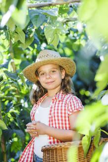 Smiling girl with basket in garden - LJF01610