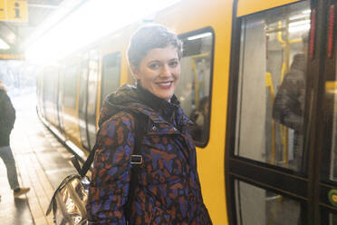 Portrait of smiling woman standing at platform, Berlin, Germany - TAMF02477