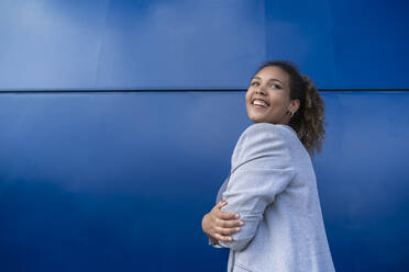 Smiling businesswoman with crossed arms in front of blue wall - SNF00436
