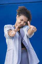 Smiling businesswoman with thumbs up in front of blue wall - SNF00439