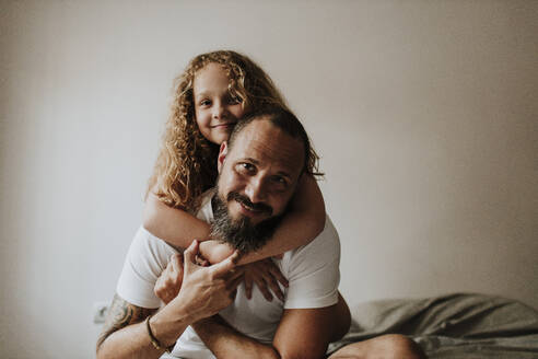 Father piggybacking daughter on bed at home - GMLF00314