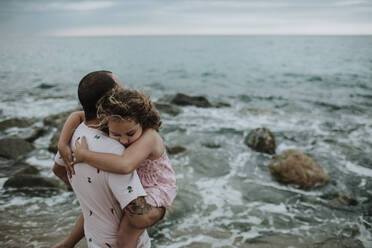 Father carrying tired daughter at beach - GMLF00323