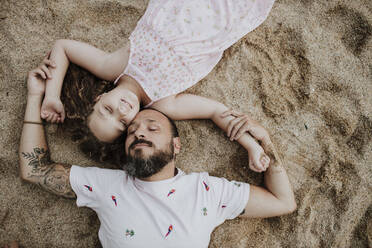 Daughter with father lying on beach - GMLF00329