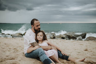 Father embracing daughter while sitting on beach - GMLF00332