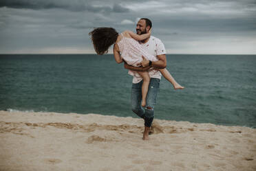 Happy father carrying daughter at beach - GMLF00335
