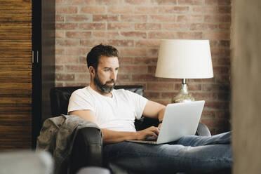 Mature man sitting in armchair, using laptop - DGOF01095