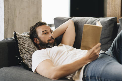 Mature man lying on couch, reading book - DGOF01098