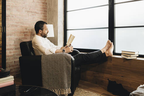 Mature man sitting in armchair by window, reading book - DGOF01122
