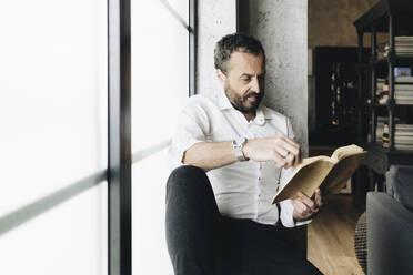 Mature man sitting on window sill, reading book - DGOF01131