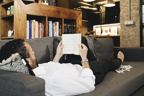 Mature man lying on couch, relaxing, reading book - DGOF01134