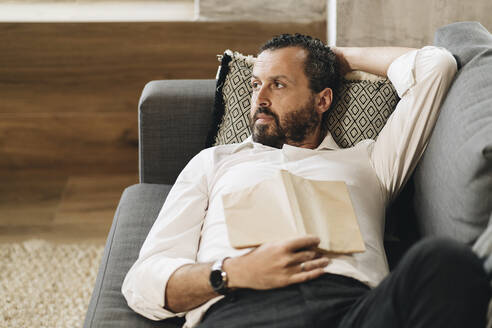 Mature man lying on couch, relaxing, reading book - DGOF01137