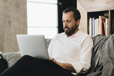 Mature man sitting on couch, using laptop - DGOF01140