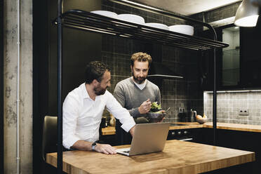 Mature friends working on laptop in kitchen, one eating salad - DGOF01155