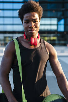 Portrait of a confident young man with headphones and basketball in the city - JMPF00037