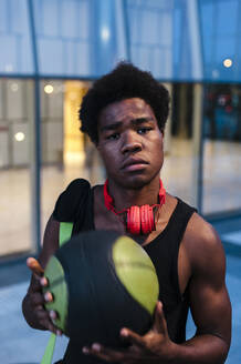 Portrait of a confident young man with headphones and basketball in the city - JMPF00040